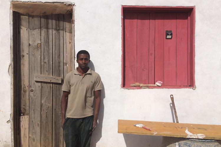 contadino, in piedi, davanti ad una casa bianca con finestra rossa a Boa Vista