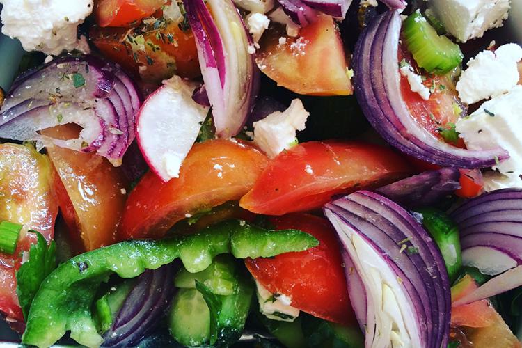 Piatto di insalata cipriota con feta, cipolle rosse, peperoni, pomodori, olive, sedano e capperi.