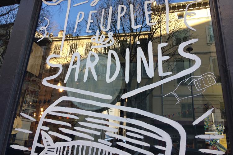 """La vetrata del ristorante La Boite à Sardine, dov'è dipinto con vernice bianca una latta di sardine stilizzata e scritto """"Il Popolo delle Sardine"""", dove mangiare a Marsiglia"""