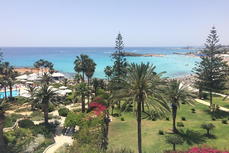 Scorcio del Nissi Beach Resort, con palme, buganville e un mare dalle incredibili sfumature.