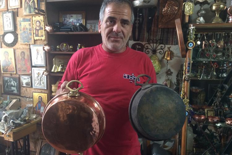 Yiangos Christodoulides nella sua bottega, dove lavora e lucida il rame.