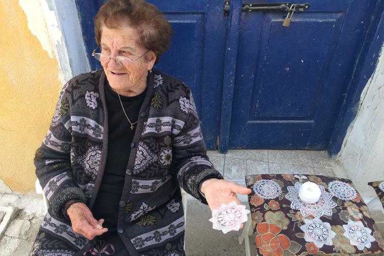 Una signora di Omodos ricama davanti a casa.