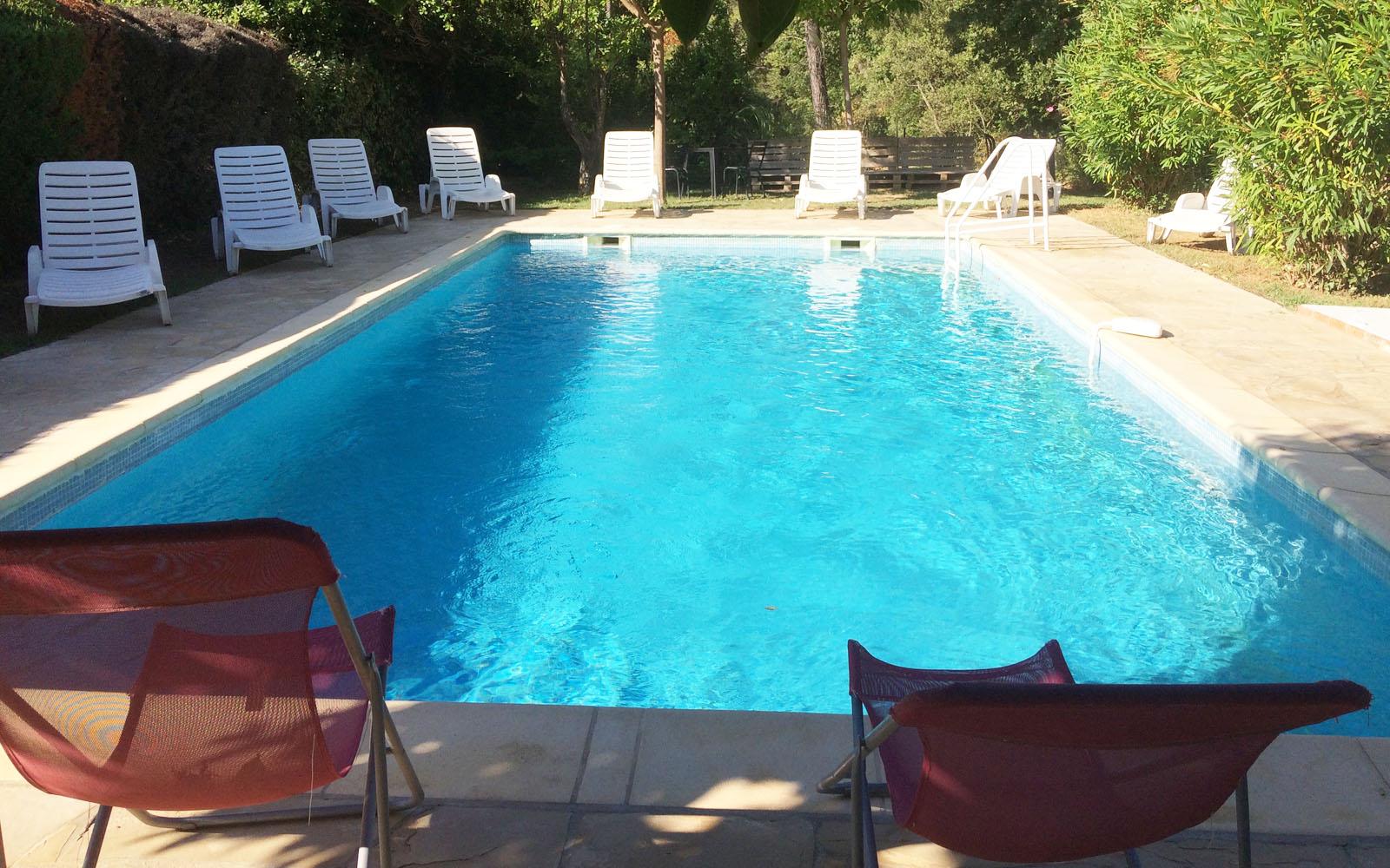 La piscina, circondata da alberi e oleandri.