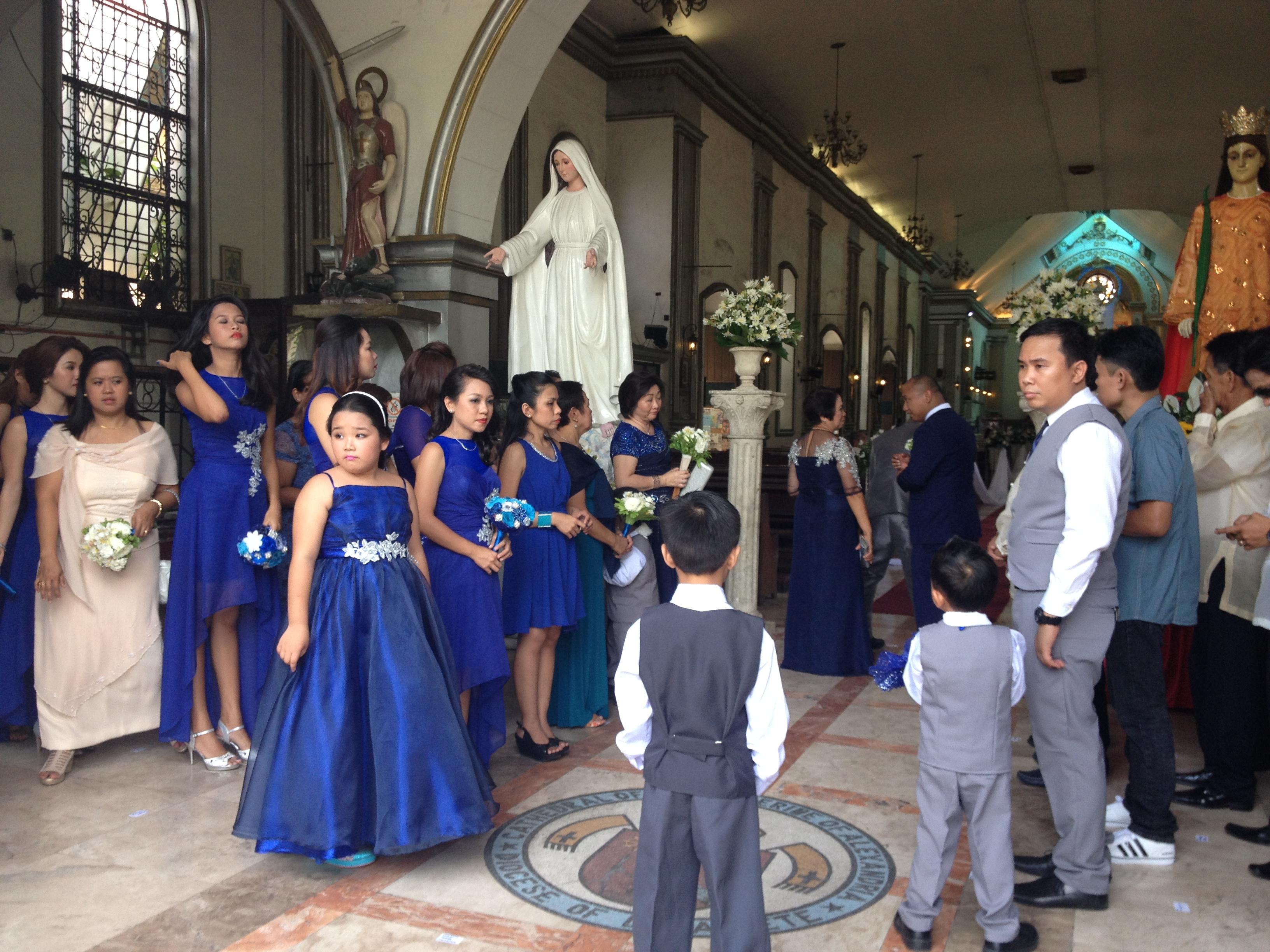 Gli ospiti aspettano la sposa ad un matrimonio nella cattedrale di Dumaguete.