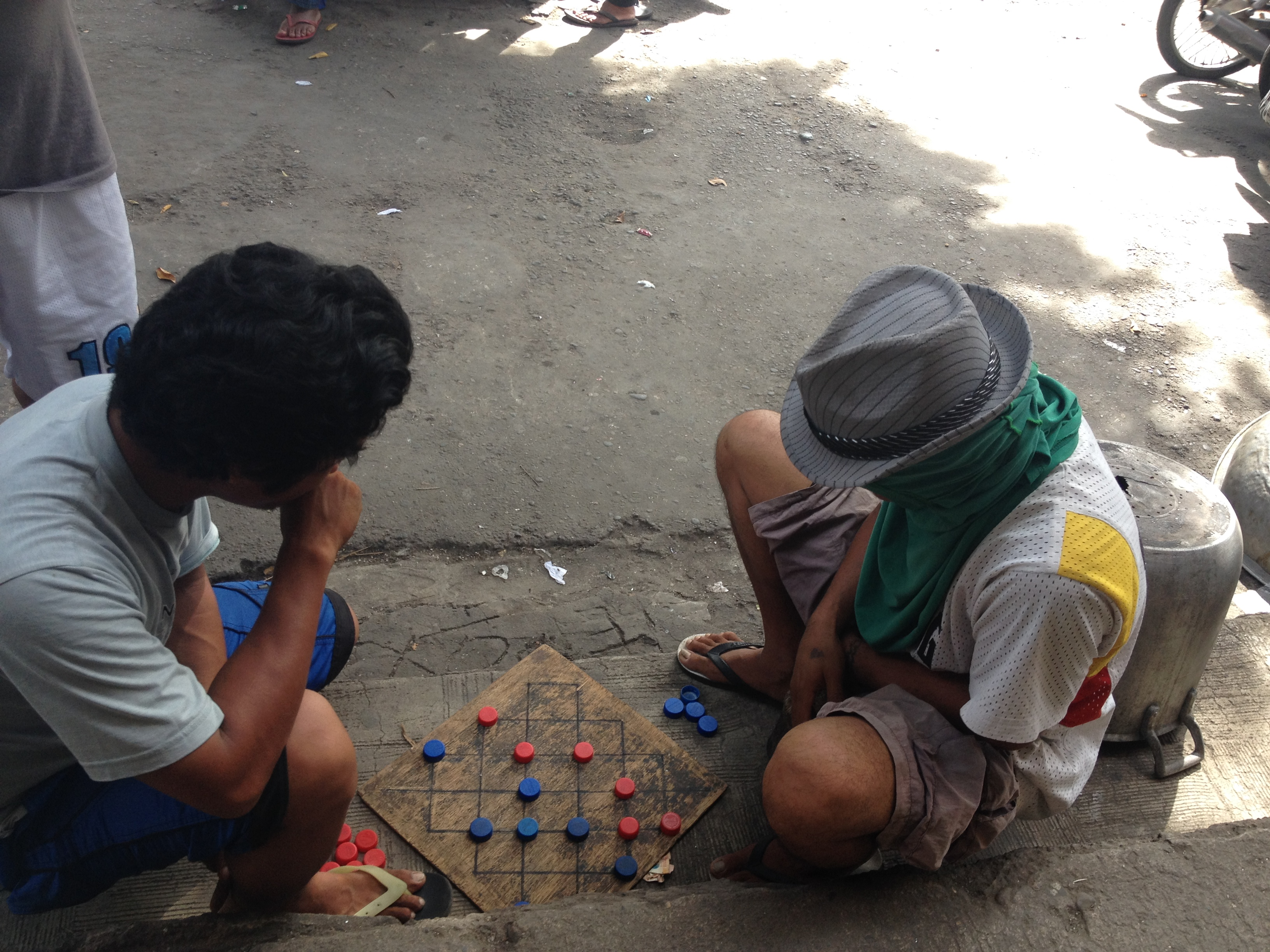 Due uomini giocano a scacchi al mercato.