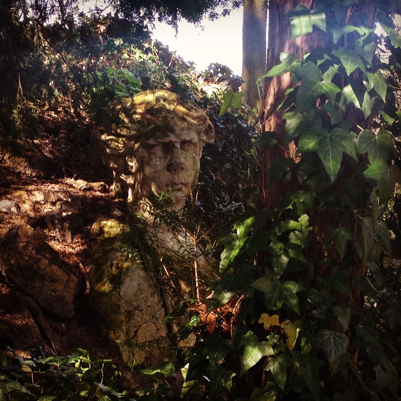 Un busto mitologico ricoperto d'edera.